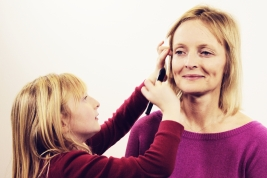 Grace makes sure to get Claire's hair out of the way before applying the makeup